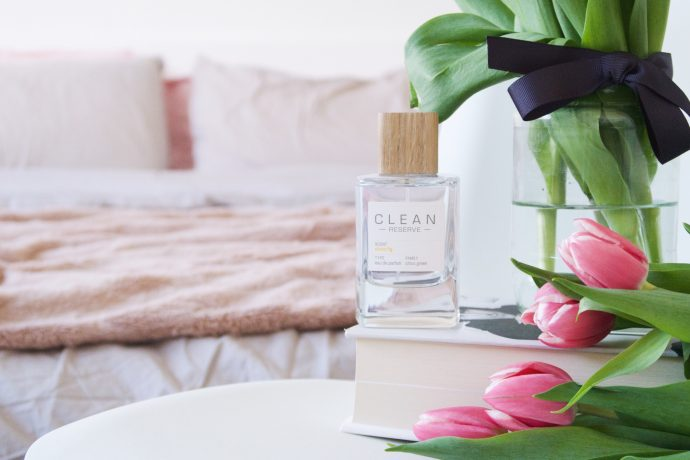a bottle of clean reserve fragrance placed on the book, next to tulips