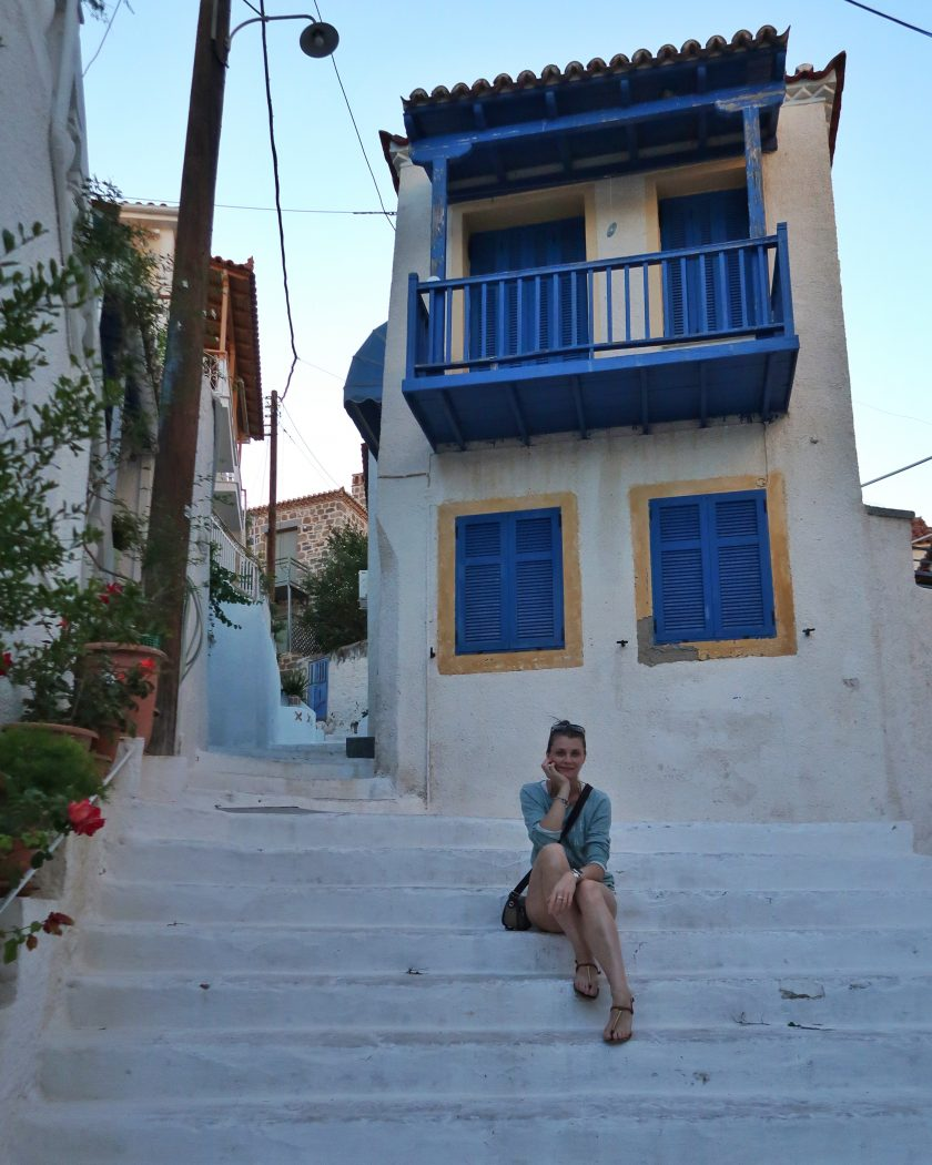 Girl on the steps on Poros, Greece at sunset.