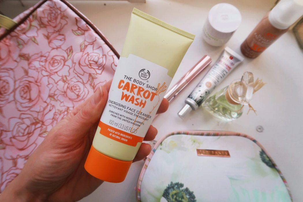 Carrot Face wash from the Body Shop  next to other beauty products.