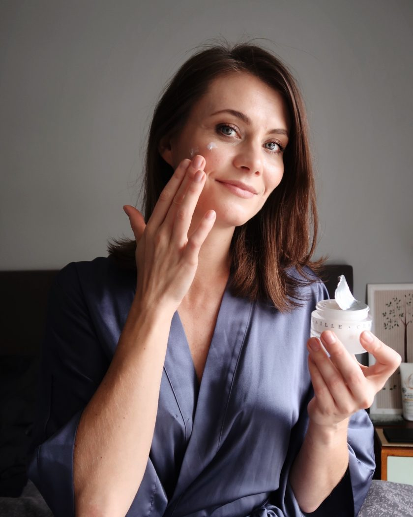 Ewa from SocialBeautify is holding Chantecaille cream blending it to her face.  Winter skincare routine.