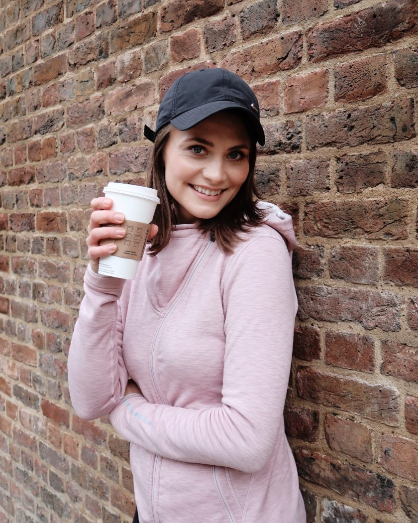 Woman in sports clothes with a cup of tea, smiling. Ewa from SocialBeautify blog.