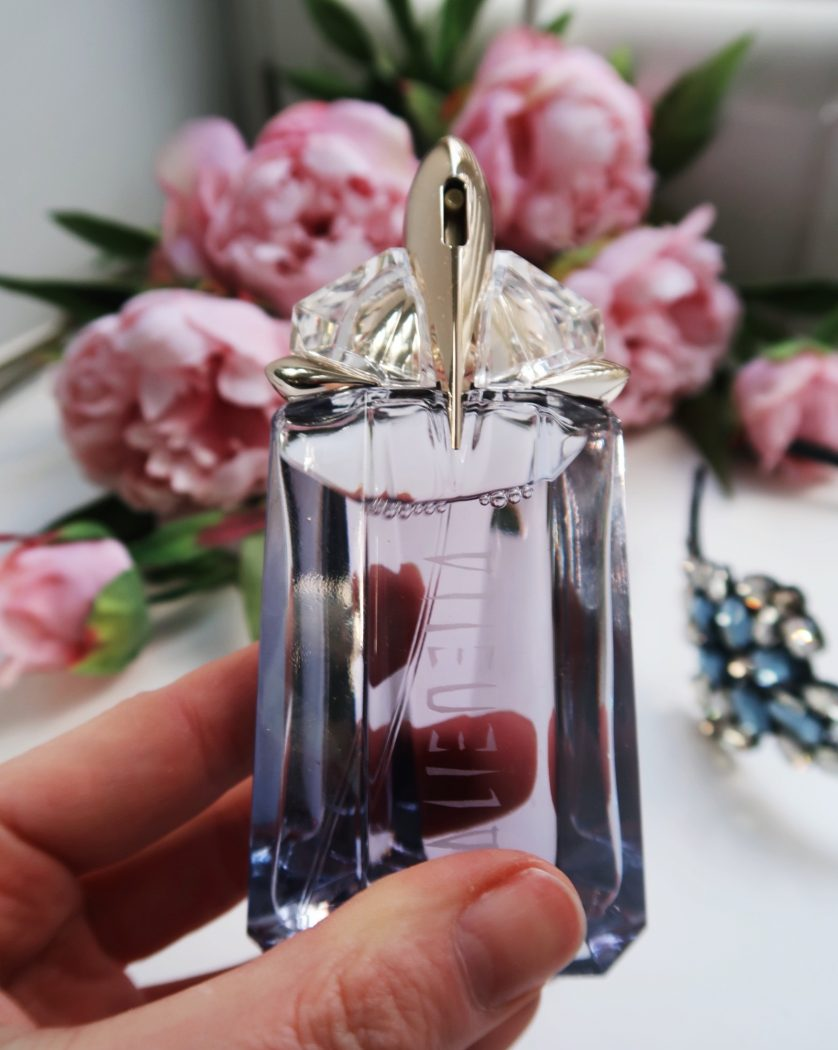 Alien by Mugler - showing bottle of Alien Mirage in hand on the background of pink flowers.