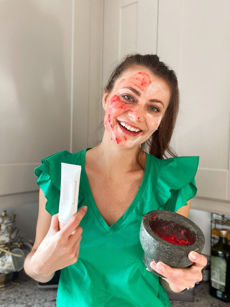 Woman smiling holding FOREO Imagination mask tube in one hand and a bowl with a DIY face mask in the other. There is a face mask on her face.