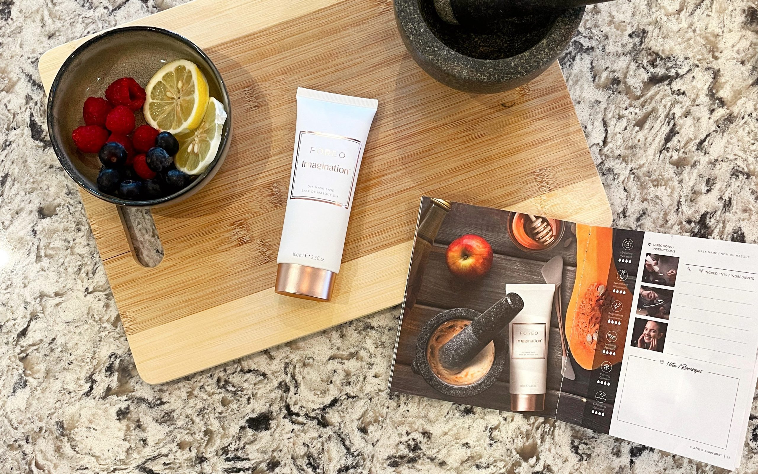 FOREO Imagination mask base and recipe book lying on the kitchen top together with fresh berries for mixing.